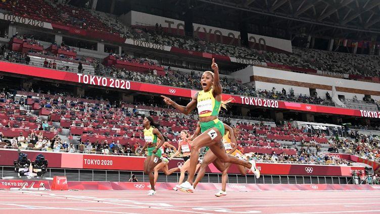 La JamaïcaineElaine Thompson-Herah franchit la ligne du 100 m féminin en tête, lors de la finale des Jeux de Tokyo, le 31 jullet 2021. (JEWEL SAMAD / AFP)