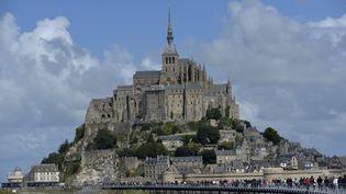 Des visiteurs se rendent au Mont-Saint-Michel, dans la Manche, le 13 août 2014. (MIGUEL MEDINA / AFP)