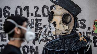 Le street-artiste Angel Crow devant une de ses oeuvres sur un mur de Paris, le 22 avril 2020, au 37e jour de confinement (MARTIN BUREAU / AFP)