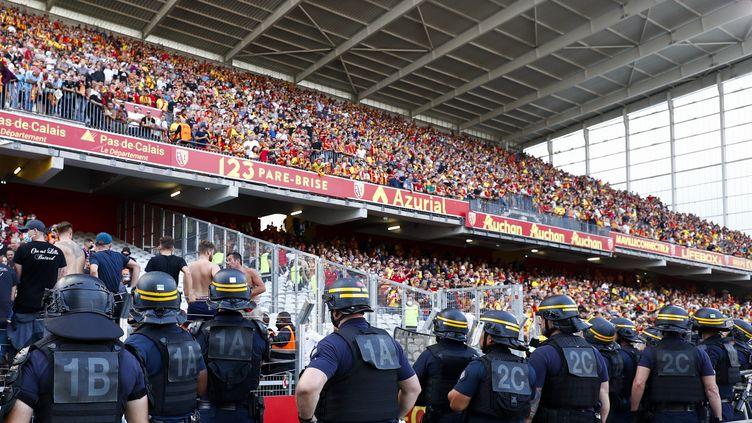 Un cordon de CRS devant les tribunes du stade Bollaert-Delelis, à Lens (Pas-de-Calais), le 18 septembre 2021, à l'occasion du derby Lens-Lille. (CATHERINE STEENKESTE / GETTY IMAGES EUROPE)