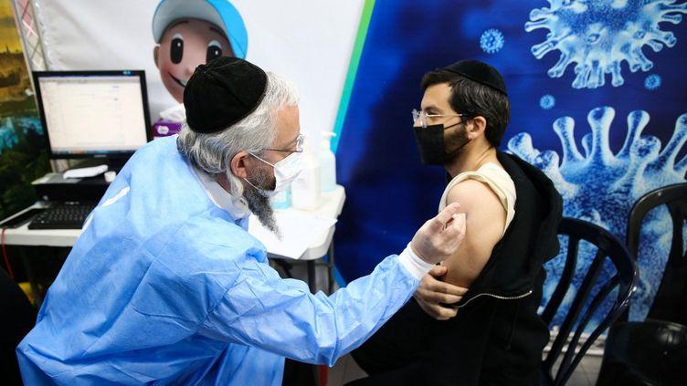 Un juif ultra-orthodoxe reçoit une dose du vaccin Pfizer-BioNtech contre le coronavirus, dans la ville israélienne de Bnei Brak, près de Tel Aviv, le 17 février 2021. (MOSTAFA ALKHAROUF / ANADOLU AGENCY / AFP)