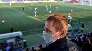 Un supporter du FC Minsk porte un masque de protection, alors qu'il assiste à un match du championnat de football, contre le FC Dinamo-Minsk, le 28 mars 2020. (SERGEI GAPON / AFP)