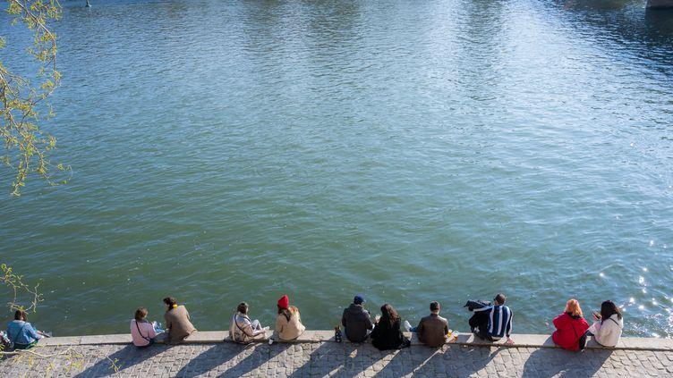 Des Parisiens prennent le soleil en bord de Seine, le 20 mars 2021. (SANDRINE MARTY / HANS LUCAS / AFP)