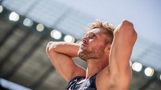 Kevin Mayer en pleine désillusion après son troisième échec au saut en longueur, le 7 août 2018, aux championnats européens de Berlin (Allemagne). (KAY NIETFELD / DPA / AFP)