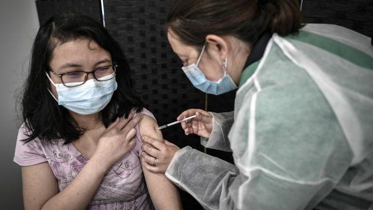 Une patiente reçoit une dose du vaccin contre le Covid-19Pfizer-BioNTechau centre de vaccination éphemère de l'Orangerie à Versailles (Yvelines), le 29 mai 2021. (STEPHANE DE SAKUTIN / AFP)