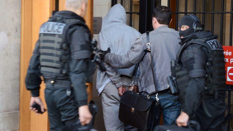 Le suspect de l'agression d'un militaire à La Défense, escorté par les policiers, le 29 mai 2013, après son arrestation. (ERIC FEFERBERG / AFP)