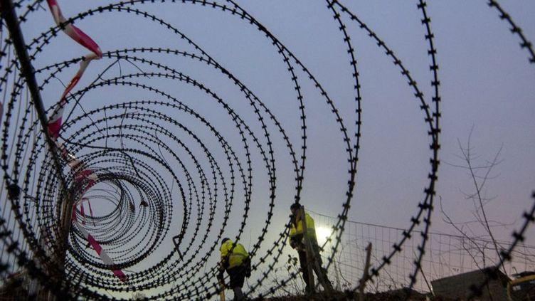 Pose d'une barrière entre l'Autriche et la Slovénie. Vienne tente de limiter l'arrivée de migrants sur son sol (9 décembre 2015). (JOE KLAMAR / AFP)