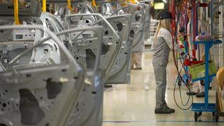 Une salariée de PSA Peugeot Citroën sur une chaîne de montage de l'usine de Mulhouse (Haut-Rhin), le 29 avril 2015. (SEBASTIEN BOZON / AFP)