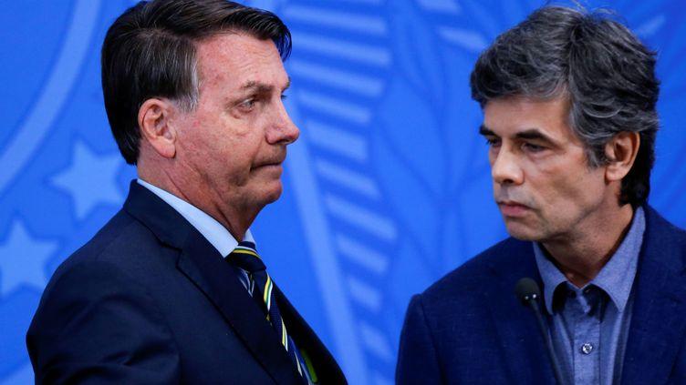 Le président brésilien, Jair Bolsonaro, aux côtés de son ministre de la Santé, Luiz Henrique Mandetta, le 16 avril 2020, à Brazilia. (ADRIANO MACHADO / REUTERS)