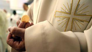Un prêtre tient dans sa main une hostie, à Nancy (photo d'illustration) (MAXPPP)