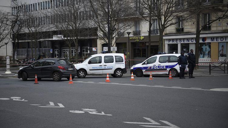 Des policiers dans le 13e arrondissement de Paris le 26 février 2016, près de l'endroit où un garçon a été renversé par un homme qui venait de voler une voiture. (LIONEL BONAVENTURE / AFP)