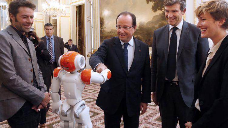 François Hollande accompagné d'Arnaud Montebourg, ministre du Redressement productif, lors de la présentation du design et de la technologie industrielle à l'Elysée, le 12 septembre 2013. (CHARLES PLATIAU / AFP)