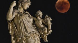 L'éclipse vue depuis la capitale grecque, Athènes, et une statue de la déesse Eiréné. (ARIS MESSINIS / AFP)