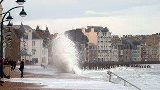 Des passants regardent les vagues s'abattant sur le front de mer à Saint-Malo, le 3 mars 2014. (DAMIEN MEYER / AFP)