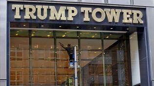 """Un homme nettoie les vitres de l'entrée d'une des """"Trump Tower"""" new-yorkaises, le 11 novembre 2016. (RICHARD DREW / AP / SIPA)"""