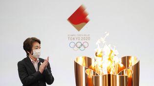 La présidente du Comité d'organisation de Tokyo 2020, Seiko Hashimoto, applaudit à côté de la vasque de célébration lors du premier jour du relais de la flamme olympique à Naraha, dans la préfecture de Fukushima, le 25 mars 2021. (KIM KYUNG-HOON / AP / SIPA)