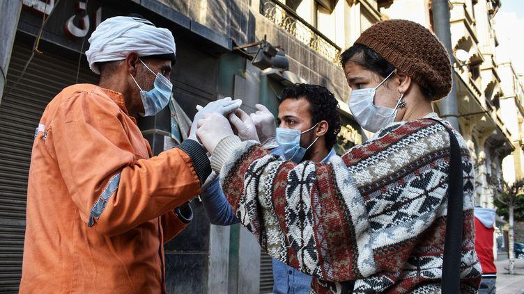 Au Caire en Egypte, des habitants portent des masques pour se protéger du coronavirus, le 21 mars 2020. (ZIAD AHMED / NURPHOTO)