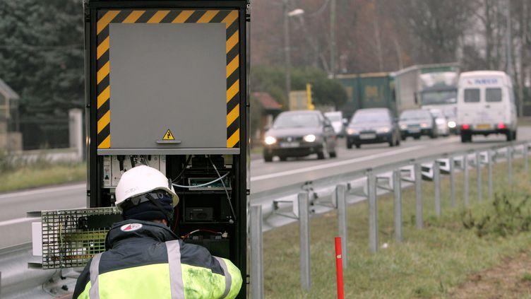 Un ouvrier procède à l'installation d'un radar automatique au bord de la nationale 2 dans le sens Paris-Soissons. (PIERRE ANDRIEU / AFP)