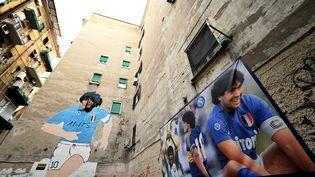 Des photos et une fresque de Diego Maradona recouvrent les murs d'un quartier de la ville de Naples (Italie) le 20 novembre 2019. (ALBERTO PIZZOLI / AFP)