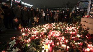 Des personnes rendent hommage aux victimes de l'attentat au camion qui a fait 12 morts et 48 blessés, à Berlin, le 20 décembre 2016. (JORG CARSTENSEN / DPA / AFP)