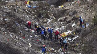Les enquêteurs et les gendarmes s'affairent, le 26 mars, au milieu des débris de l'airbus A320 de la Germanwings, écrasé deux jours plus tôt dans les Alpes par son copilote Andreas Lubitz. (ANNE-CHRISTINE POUJOULAT / AFP)