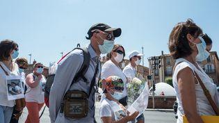 Cédric Jubillar (au centre) participe avec son fils à une marche à Albi (Tarn) le 12 juin 2021, suite à la disparition de l'infirmière de 33 ans en décembre 2020. (FRED SCHEIBER / AFP)