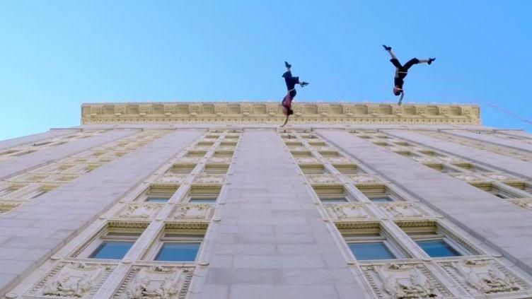 Capture d'écran - Amelia Rudolph et Roel Seeber du groupe Bandaloop dansent accrochés à des fils, à la verticale de l'hotel de ville d'Oakland en CCalifornie (GOPRO / BANDALOOP / YOUTUBE)
