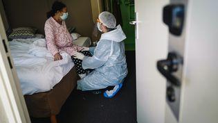 Un médecin au chevet d'une patiente souffrant de Covid-19 dans un hôtel accueillant des malades à Chelles, près de Paris, le 22 avril 2020. (LUCAS BARIOULET / AFP)