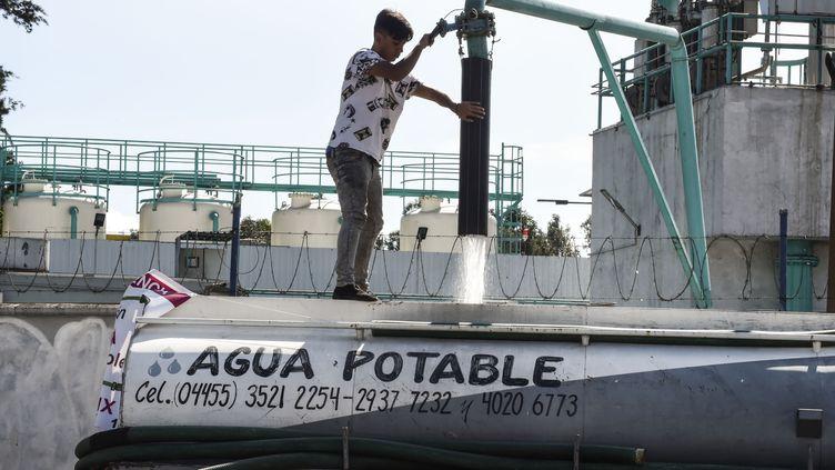 Un homme remplit un camion citerne d'eau potable, le 5 novembre 2018, à Mexico (Mexique). (Alfredo ESTRELLA / AFP)