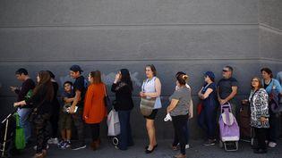 Une queue à l'entrée d'un supermarché de Santiago (Chili), le 22 octobre 2019. (PABLO VERA / AFP)