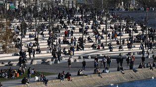 Des habitants sont assis le long du quai du Rhône, à Lyon (Rhône), le 25 mars 2021. (PHILIPPE DESMAZES / AFP)