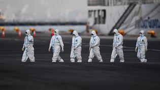 """Des personnes en tenue de protection près du paquebot """"Diamond Princess"""" dont les 3 600 passagers sont placés en quarantaine dans le port de Yokohama (Japon),le 10 février 2020. (CHARLY TRIBALLEAU / AFP)"""