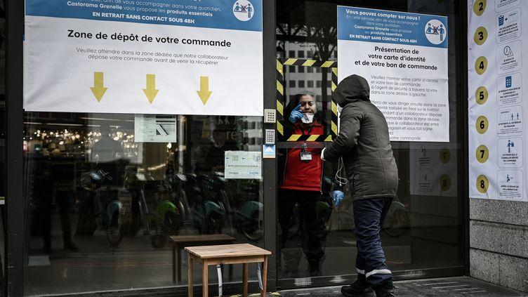 Un client se renseigne devant un magasin de bricolage à Paris, le 2 avril 2020. (PHILIPPE LOPEZ / AFP)