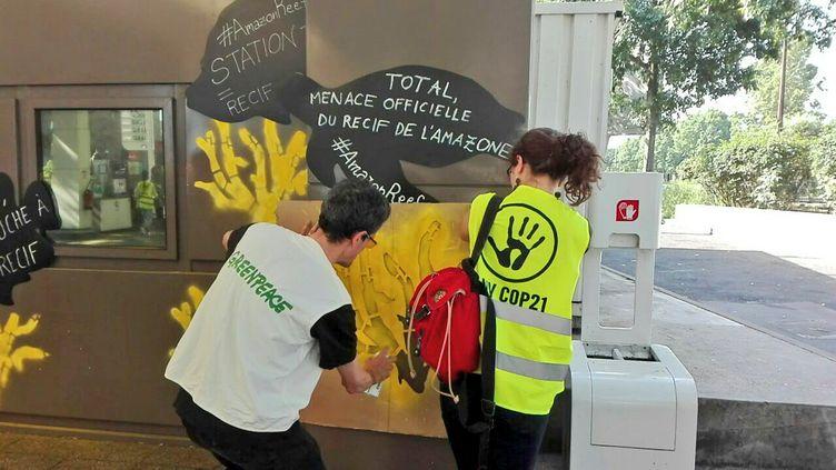 Des militants de l'organisations écologistes Greenpeace et ANV COP21 redécorent une station service Total, le 27 mai 2017. (ANV COP21)