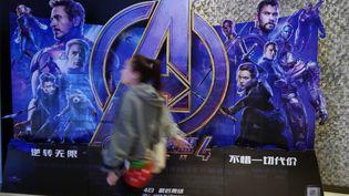 """Une femme passe devant une pancarte promotionnelle pour le film """"Avengers : Endgame"""" dans un un cinéma de Yichang, en Chine, le 13 mai 2019. (YI CHANG / IMAGINECHINA / AFP)"""