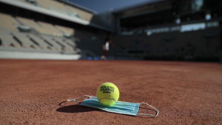 Une balle de l'édition 2020 et un masque sur le Court central de Roland-Garros (STEPHANE ALLAMAN / STEPHANE ALLAMAN)