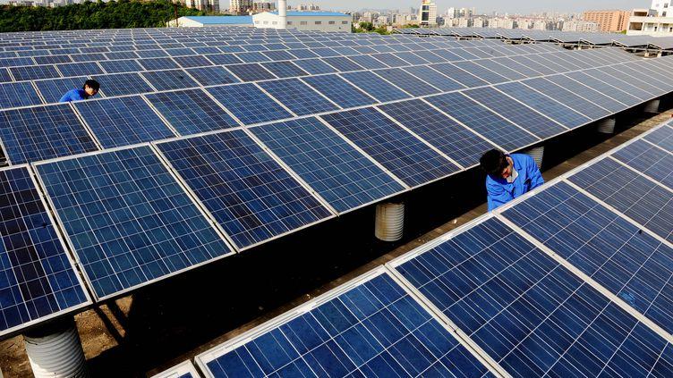 Des ouvriers installent des panneaux solaires sur le toit d'un immeuble, à Shangrao, en Chine, le 27 avril 2013. (ZHUO ZHONGWEI / IMAGECHINA / AFP)