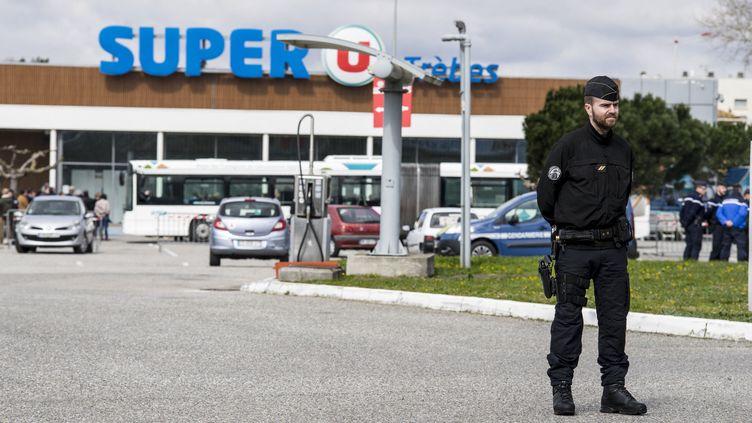 Un gendarme monte la garde devant le Super U de Trèbes (Aude), le 26 mars 2018. (IDRISS BIGOU-GILLES / HANS LUCAS / AFP)