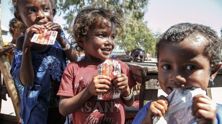 Des enfants du village de Befeno dans l'île de Madagascar mangent des compléments alimentaires distribués par Médecins sans Frontières pour combattre la famine, le 2 septembre 2021. (RIJASOLO / AFP)