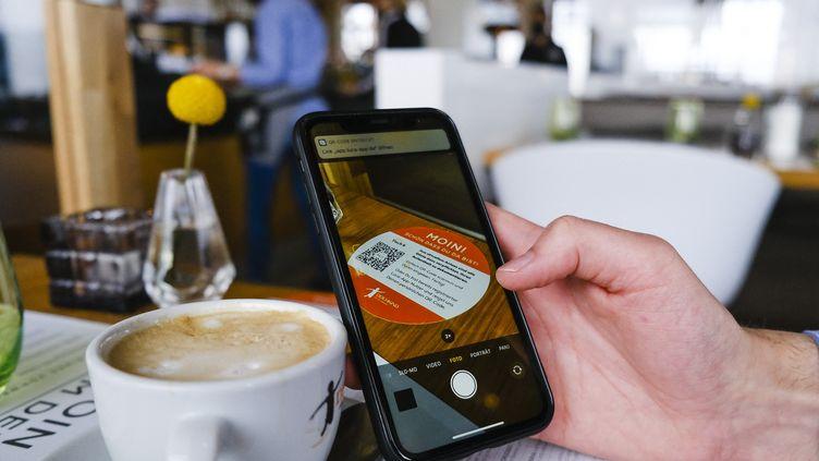 Le client d'un café scanne un QR code àSankt Peter-Ording (Allemagne), le 1er mai 2021. (FRANK MOLTER / DPA / AFP)