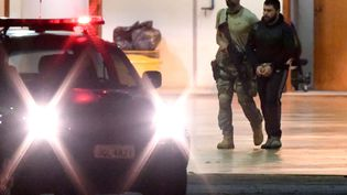 """Un suspect terroriste est escorté par la police fédérale brésilienne lors de l'""""Opération Hashtag"""". (EVARISTO SA / AFP)"""