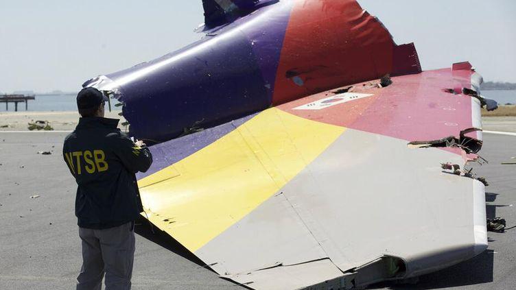 Un enquêteur américain examine une partie des restes du Boeing 777 d'Asiana Airlines, qui s'est écrasé samedi 6 juillet à l'aéroport de San Francisco (Etats-Unis). (NTSB)