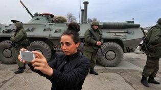 A Feodosiya le 2 Mars 2014, une jeune femme se prend en photo avec les soldats russes. (AFP)