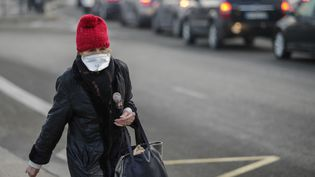 Une femme traverse la place Maillot, à Paris, le 23 janvier 2017, un jour de mesures antipollution dans la capitale. (GEOFFROY VAN DER HASSELT / AFP)