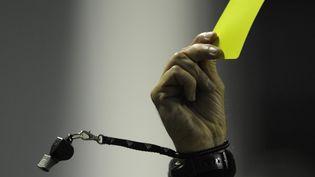Un carton jaune et un sifflet à la main d'un arbitre de football. (JUAN MABROMATA / AFP)