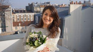 Déborah de Robertis pose avec le bouquet composépour sa dernière performance, le 20 janvier 2016, à Pantin (Seine-Saint-Denis). (JULIE RASPLUS / FRANCETV INFO)