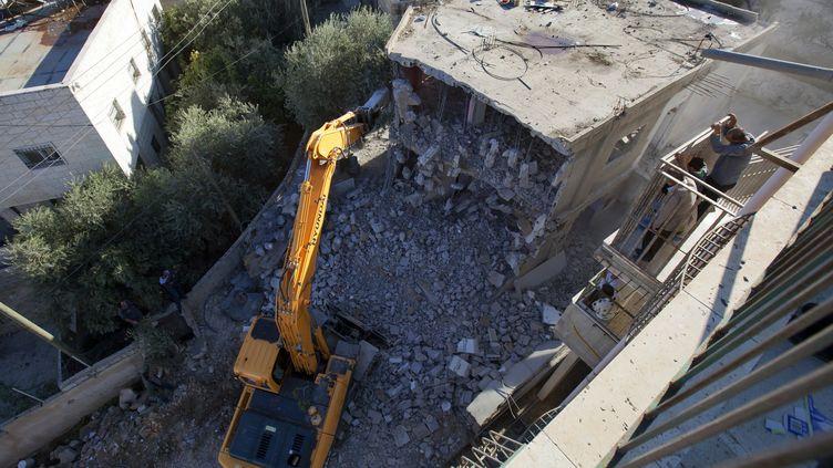 A Jérusalem-Est, un bulldozer détruit une maison palestinienne, le 30 novembre. (AHMAD GHARABLI / AFP)