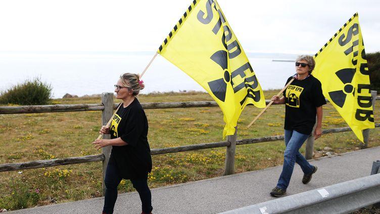 Des activistes de Greenpeace marchant contre le nucléaire devant le site de Flamanville, le 28 juin 2018. (CHARLY TRIBALLEAU / AFP)