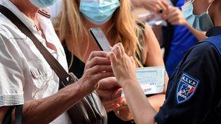 Une agente de la mairie de Fréjus (Var) contrôle le pass sanitaire d'un homme à l'entrée d'un spectacle de Jean-Marie Bigard, le 23 juillet 2021. (LIONEL URMAN / SIPA)