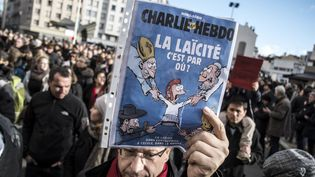 Un manifestant de la marche républicaine du 11 janvier 2015 brandit une Une de Charlie Hebdo sur la laïcité. (JEAN-PHILIPPE KSIAZEK / AFP)